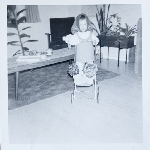 Klein meisje achter poppenwagen