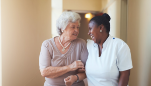 Verzorgende en oudere dame arm in arm lachend in wandelgang