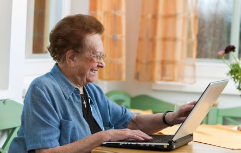 Oude dame lachend achter laptop