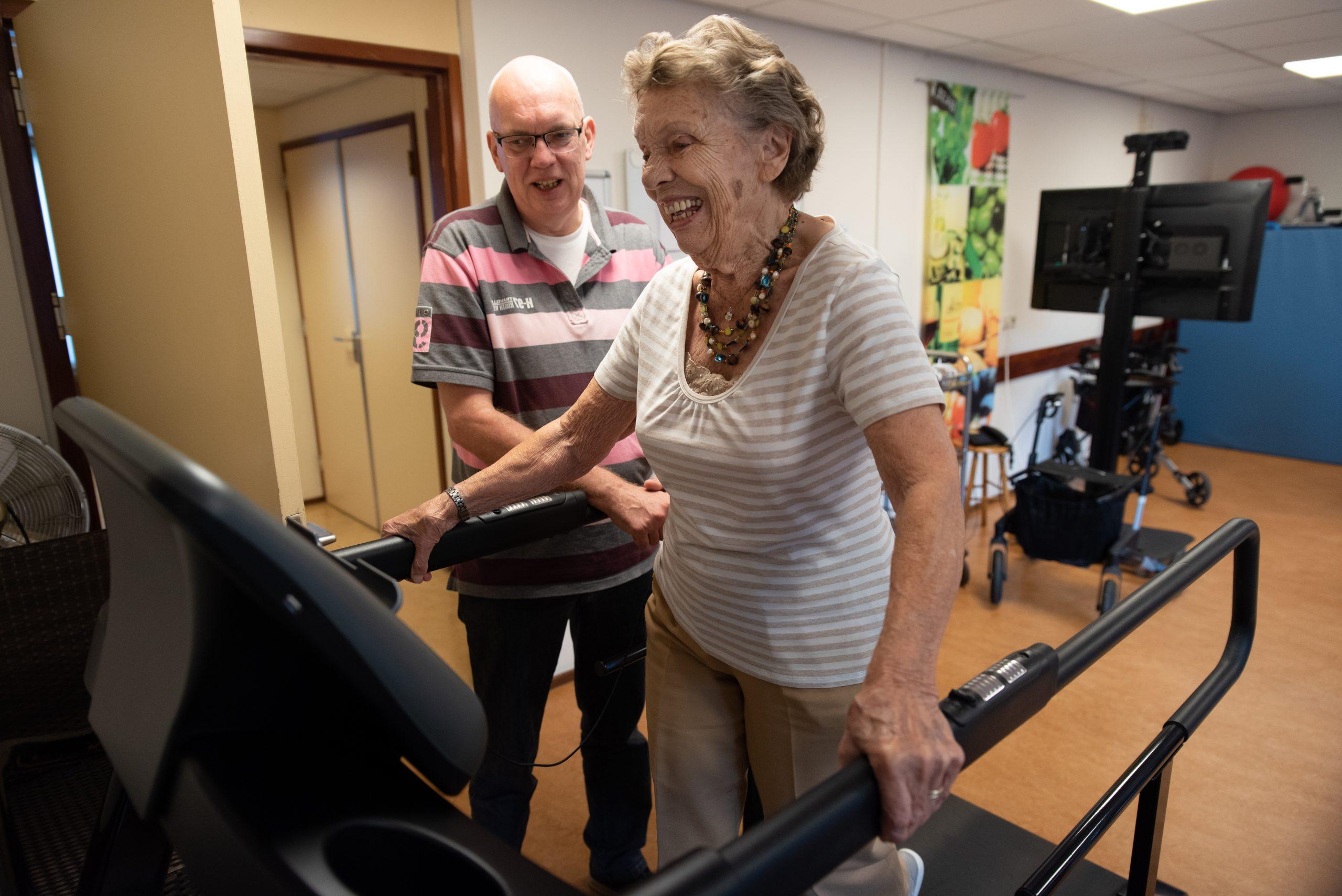Mannelijke zorgmedewerker helpt oudere dame op loopband