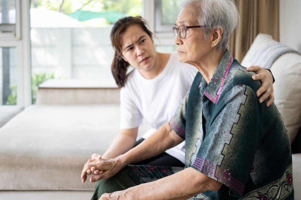 Verontruste bewoner op bankje met peinsende zorgmedewerker